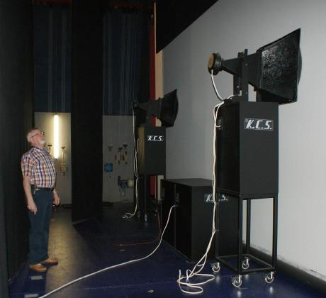 Steen Rasmussen viser frem to av de tre frontkanalene. Kinolerretet er akustisk transparent, så de enorme høyttalerne kan plasseres korrekt i forhold til bildet.