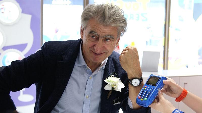 Swatch-sjefen Nicolas Hayek, demonstrerer trådløs betaling med Swatch-klokken.